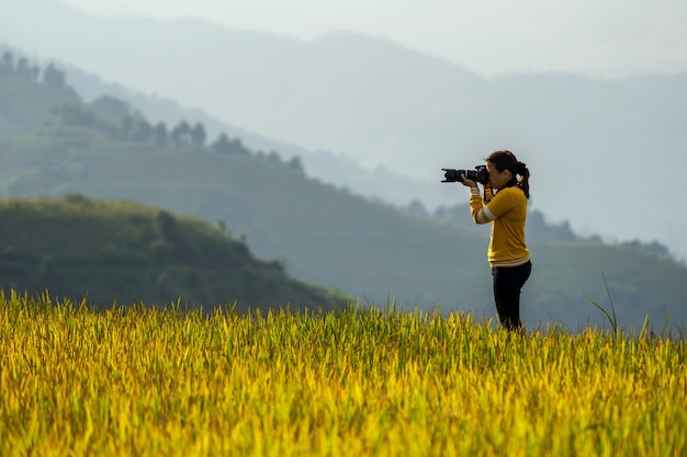 Back side of photographer taking photo over the rice fields
