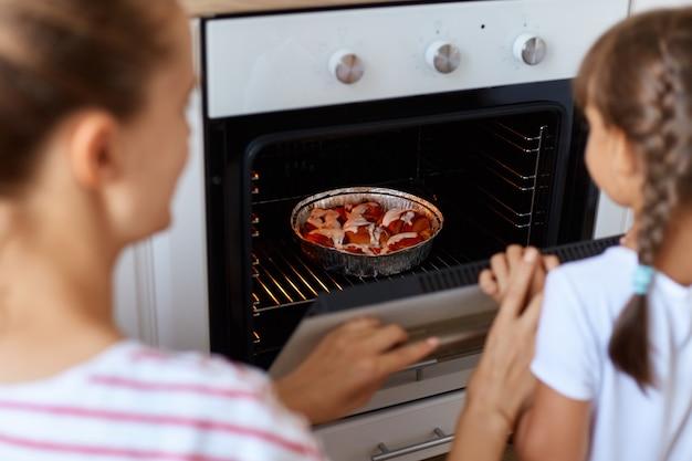 オーブンのベーキング皿にクロワッサンを入れている若い女性の裏側の肖像画、彼女の娘は近くに立ってガスストーブの中を見て、できるだけ早く美味しく味わいたいと思っています。