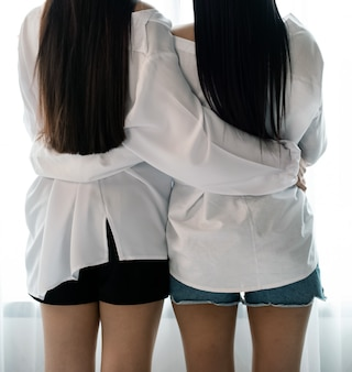 Back side of two women hug each other beside window, romantic love couple