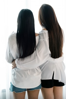 Back side of two women hug each other beside window, romantic love couple