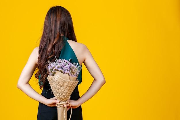 Фотография заднего вида вьющихся волос азиатская женская брюнетка, держащая букет цветов с веселой и счастливой, студийной съемкой, изолированной на ярко-желтом фоне.