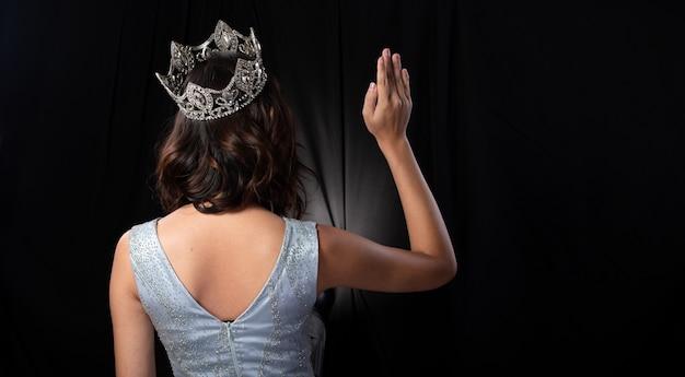 背面図スパンコールのミスページェント美人コンテストの肖像イブニングボールガウンロングドレススパークルライトダイヤモンドクラウン、アジアの女性のファッションは黒い髪のスタイルを構成し、スタジオ照明の暗い背景