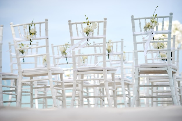 Back side of white chiavari chairs with cone of rose petals on the sand for beach wedding venue preparation