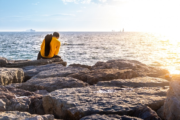Back side of young man sitting on rocks by the sea