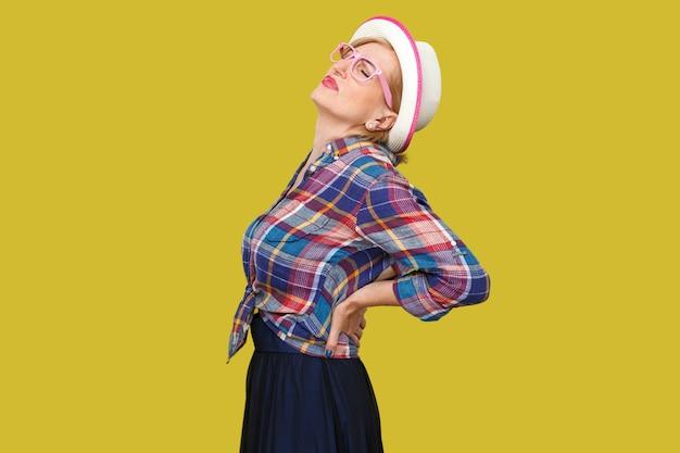 Боль в спине, позвоночнике или почках. профиль вид сбоку портрет современной стильной зрелой женщины в повседневном стиле с шляпой, стоящей и держащей ее болезненную спину. крытая студия выстрел, изолированные на желтом фоне.