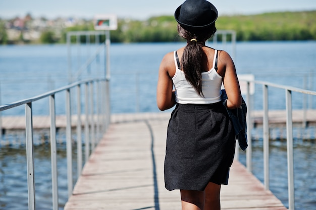 Back of stylish african american model in glasses hat, jeans jacket and black skirt posed outdoor on pier against lake.