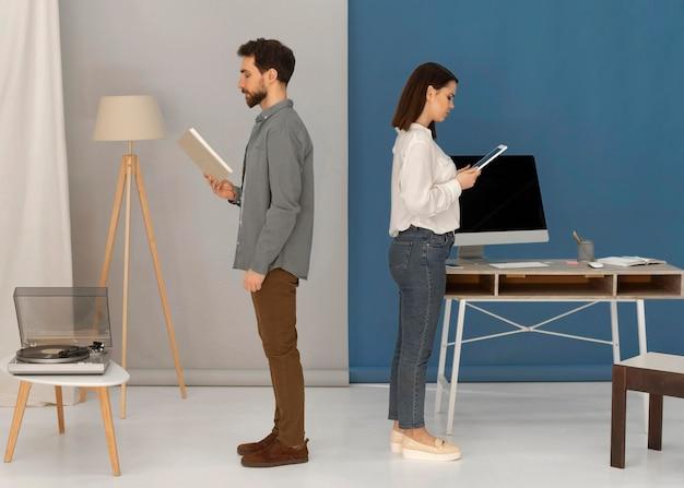 Спиной к спине мужчина с книгой и женщина с планшетом