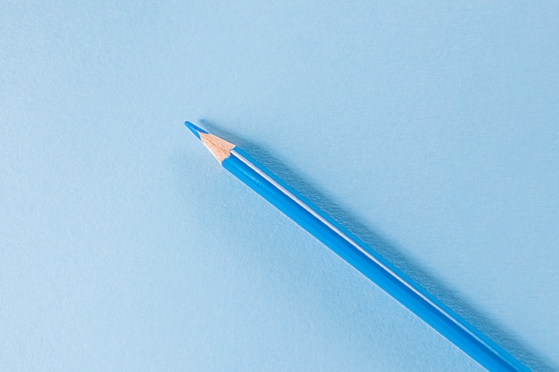 Обратно в школу. синий карандаш стоит на синем пространстве. монохромное изображение. креативная концепция детского творчества, рисования.