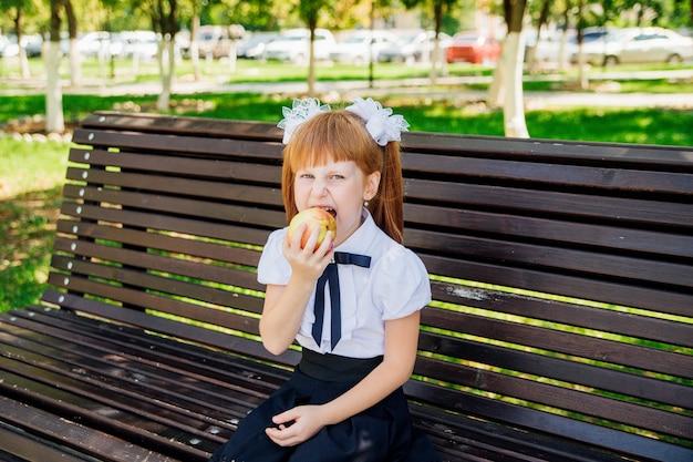 Обратно в школу. симпатичная школьница сидит на скамейке во дворе школы и кусает зеленое яблоко. правильное школьное питание на обед. маленькая девочка идет в первый класс. день знаний.