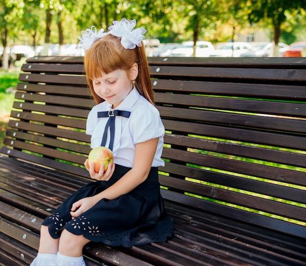 Обратно в школу. симпатичная школьница сидит на скамейке во дворе школы и держит в руках зеленое яблоко. правильное школьное питание на обед. маленькая девочка идет в первый класс.