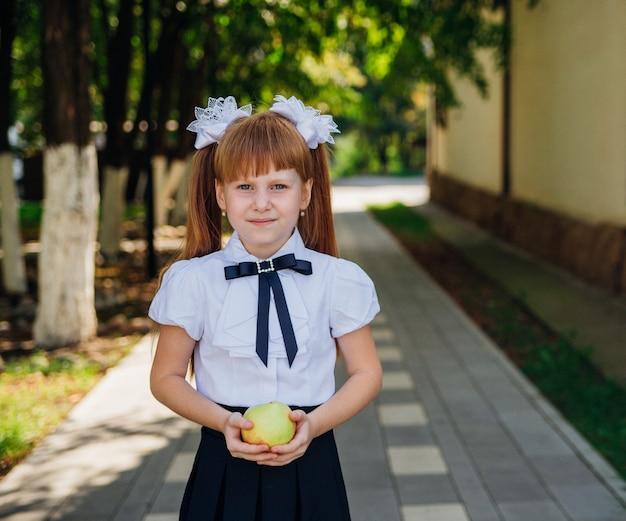 Обратно в школу. симпатичная школьница стоит в парке или во дворе школы и держит в руках зеленое яблоко. правильное школьное питание на обед. маленькая девочка идет в первый класс.