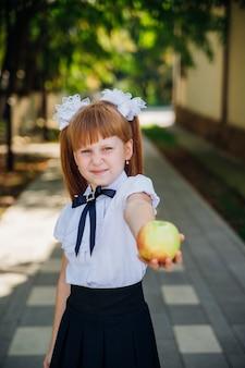 学校に戻る。かわいい小さな女子高生が公園や校庭に立って、青リンゴを持っています。