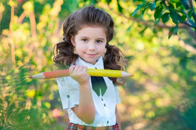 Обратно в школу. симпатичная школьница держит в руках карандаши, улыбаясь в камеру. образование. понятие рекламы и людей.