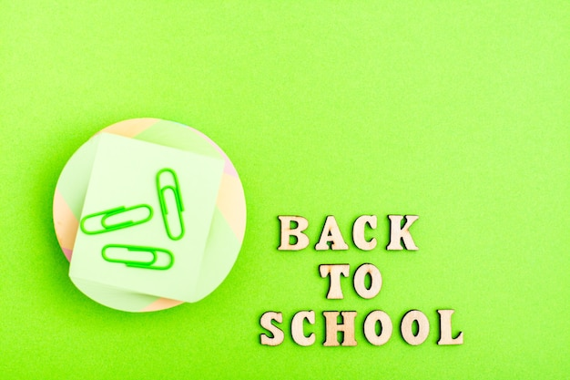 Обратно в школу. стопка листов для письма, скрепки и надпись деревянными буквами на зеленом фоне