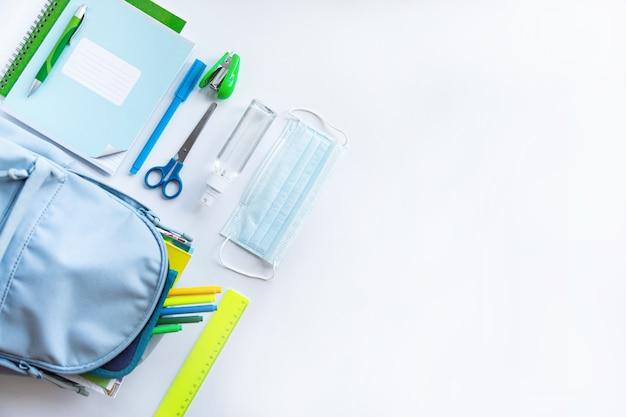 Снова в школу после пандемии коронавируса. рюкзак, канцелярские товары, антисептик, маска для лица на белом фоне.