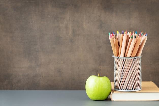 학교 및 교육 개념으로 돌아가서 칠판 근처에 있는 나무 색연필과 교과서의 녹색 사과 케이스 및 텍스트 위치