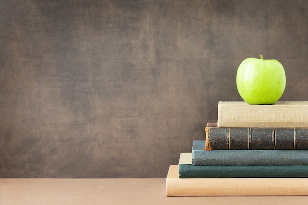 Снова в школу и концепцию образования зеленое яблоко на вершине стопки книг возле доски и место для текста