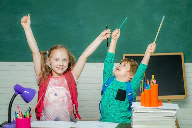 学校に戻って幸せな時間の子供は背景に黒板で答える準備ができています