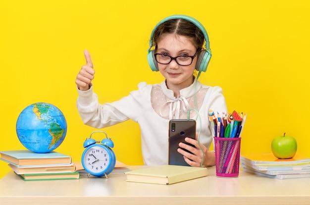 Снова в школу и счастливое время. милый трудолюбивый ребенок сидит за столом в помещении. ребенок учится в классе на желтом фоне. счастливая улыбающаяся маленькая девочка с большим пальцем вверх