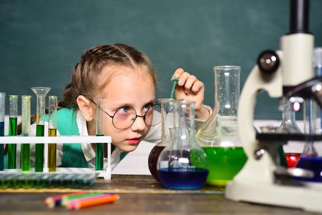 学校に戻り、ホームスクーリング。科学と教育の概念。試験管で実験をしている幸せな小さな科学者。ポートレアはクローズアップ。