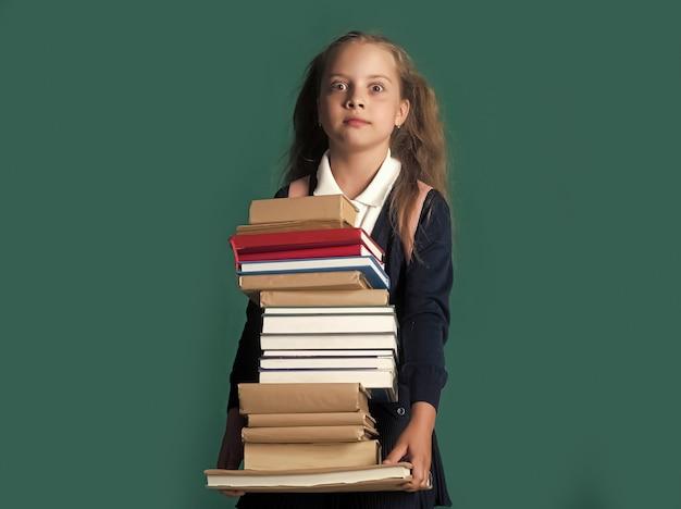 다시 학교와 숙제 개념. 충격을받은 얼굴을 가진 여학생은 거대한 책 더미를 보유하고 있습니다.