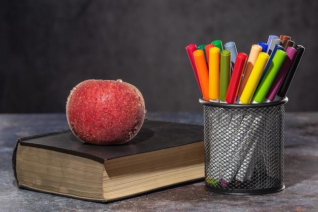 Обратно в школу. яблоко в каплях воды, лежащих на книге, рядом с разноцветными маркерами, стоящими на подставке