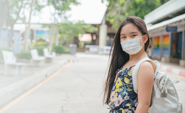 Обратно в школу. азиатская девушка ребенка носить маску с рюкзаком, ходить в школу. пандемия коронавируса. новый нормальный образ жизни. концепция образования.