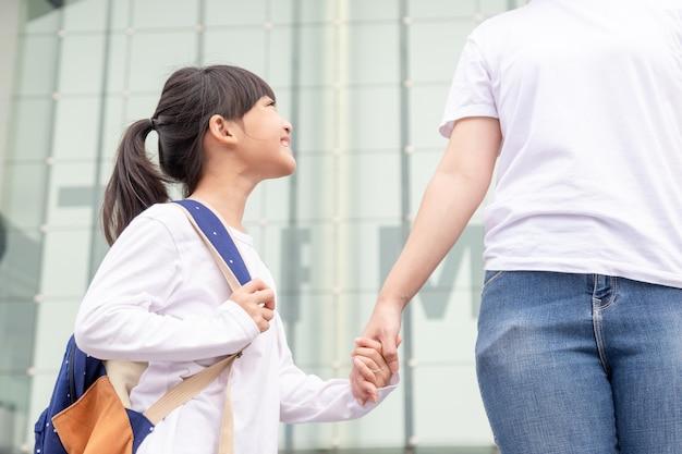 Обратно в школу. азиатская девочка ученика матери и дочери с рюкзаком, держащим руку и вместе идущим в школу. начало уроков. первый день