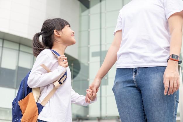学校に戻るバックパックを持って手を握って学校に行くアジアの母と娘の生徒の女の子