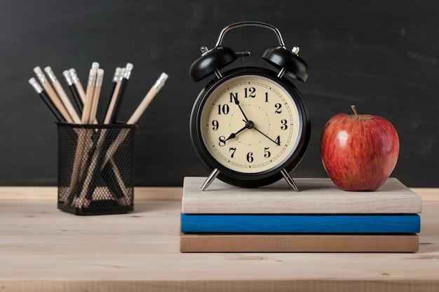 Обратно в школу фон с будильником, яблоком и карандашами на фоне доски