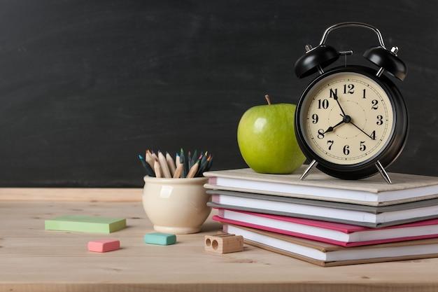 Обратно в школу фон с будильником, яблоком, тетрадями и карандашами на фоне доски