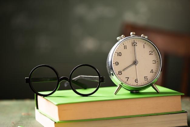 本と黒板の目覚まし時計で学校の背景に戻ります。学校に戻るコンセプト