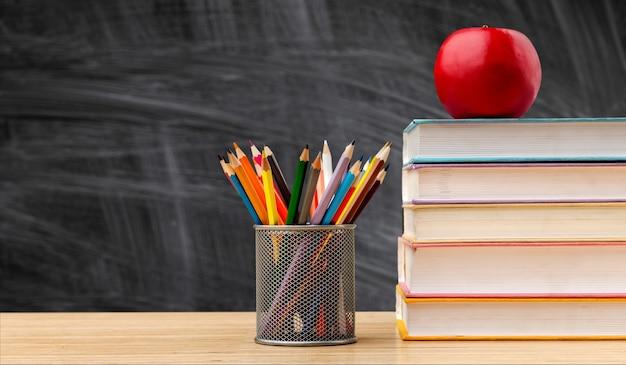 Обратно в школу фон с книгами и яблоком на доске