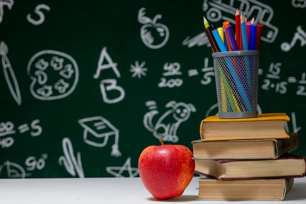 学校の背景に本、鉛筆、白いテーブルの上のリンゴ。