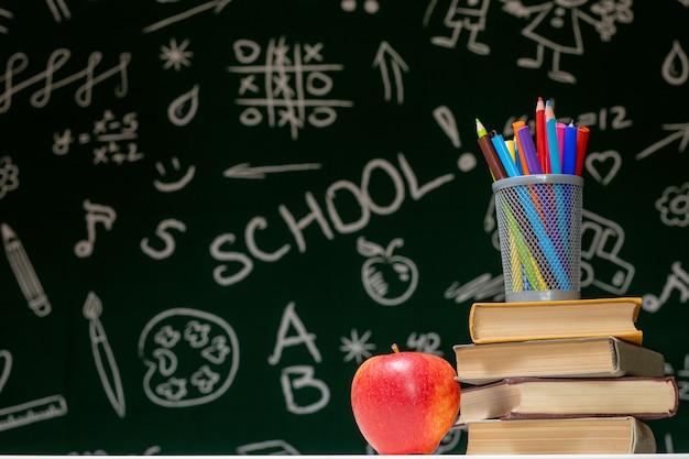 Снова в школу фон с книгами, карандашами и яблоком на белом столе.