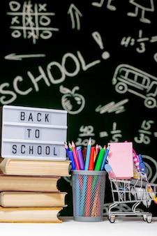 本、鉛筆、緑の黒板背景の白いテーブルの上の地球と学校の背景に戻る。