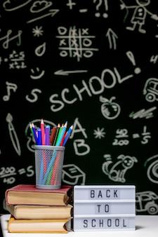 本、鉛筆、緑の黒板背景の白いテーブルにグローブと学校の背景に戻る
