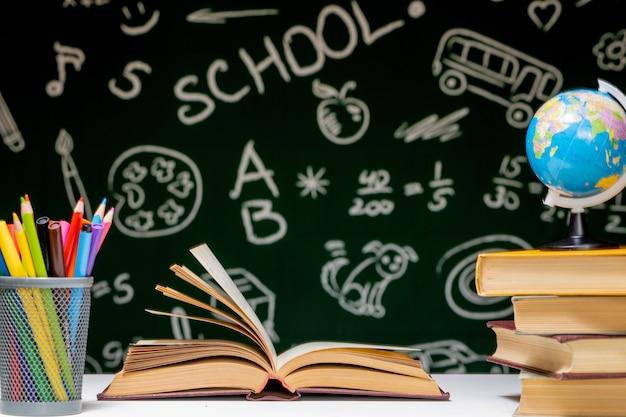 녹색 칠판 배경에 흰색 테이블에 책, 연필, 글로브와 함께 학교 배경으로 돌아갑니다.