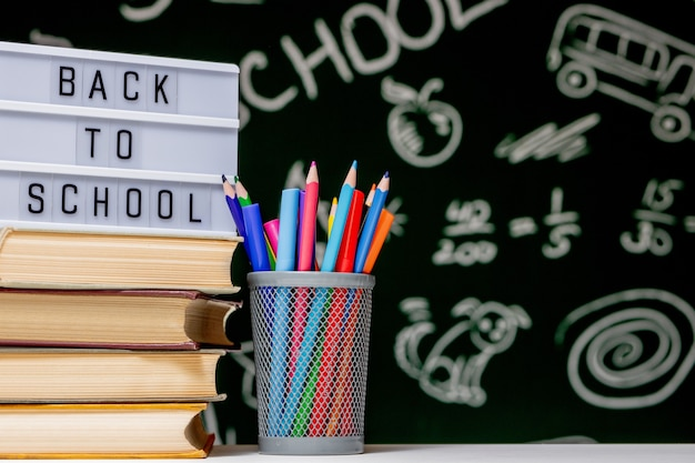 Обратно в школу с книгами, карандашами и глобусом на белом столе