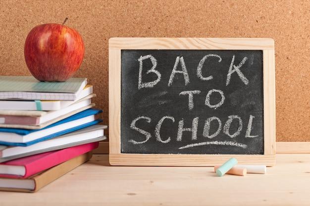 黒板、本、赤いリンゴで学校の背景に戻る