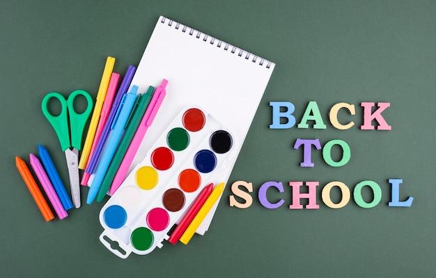 色鉛筆とノートで学校の背景に戻る