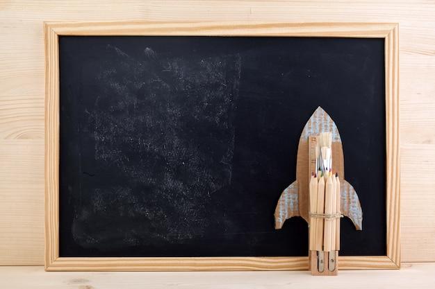 Обратно в школу фон с ракетой из карандашей и кистей
