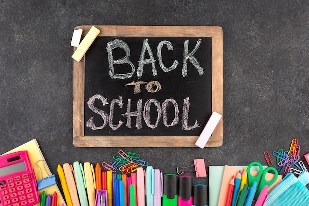 黒板に学用品を持って学校の背景に戻る
