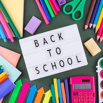 学用品とライトボックスで学校の背景に戻る