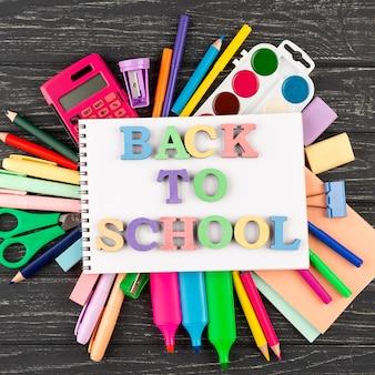 学用品とノートブックで学校の背景に戻る