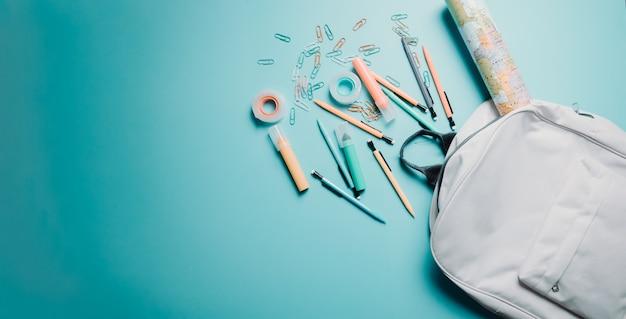 黒板に学用品を持って学校の背景に戻ります。鉛筆、バッグ、ペン、段ボール、カラフルな背景