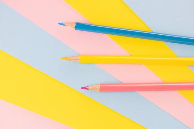 Обратно в школу. синие, розовые и желтые карандаши лежат на пространстве одного цвета. креативная минималистичная концепция детского творчества, рисования.