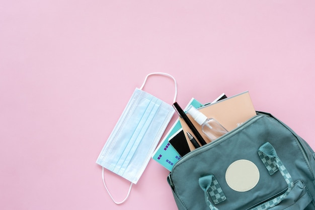 Обратно в школу. яркие красочные школьные принадлежности и рюкзак для школы или колледжа на розовом фоне с защитной маской и антибактериальным спреем. баннер