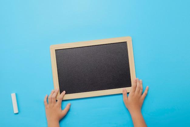 学校に戻って、チョークと黒板を保持している手