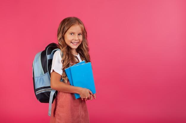 Обратно в школу. веселая счастливая девушка с синим рюкзаком на розовом фоне.